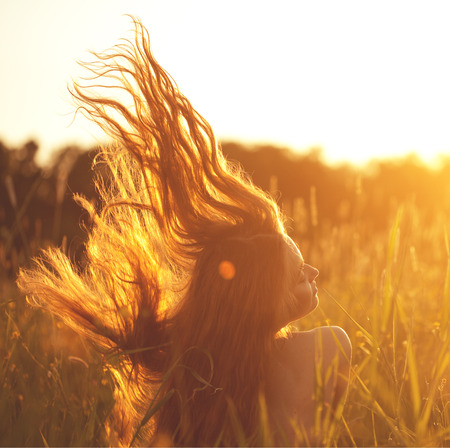 Beautiful smiling woman in a field at sunset. Trendy young girl at sunset with flying hair Stok Fotoğraf