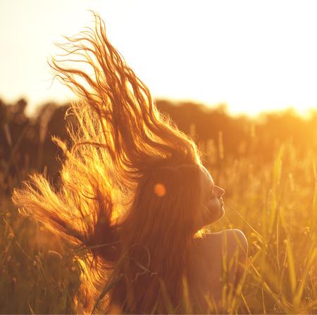 Krásná usmívající se žena v poli při západu slunce. Módní mladá dívka při západu slunce s létající vlasy