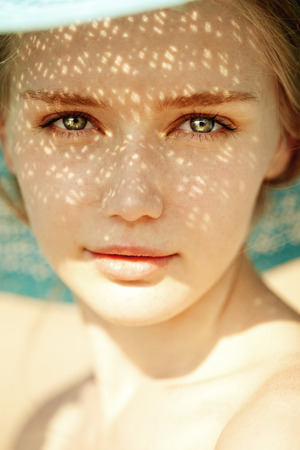 帽子はクローズ アップで美しい女性の美しさの肖像画。彼女の顔に太陽の光線とトレンディな女の子の美しさの肖像画