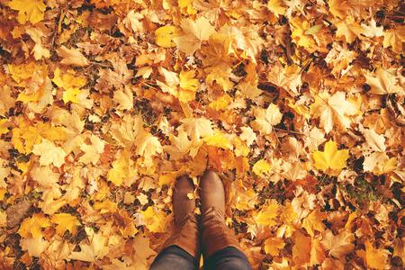 Conceptueel beeld van benen in laarzen op de herfstbladeren. Voeten schoenen wandelen in de natuur