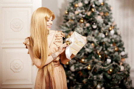 make a gift: Luxury blonde in interior New Year. Young beautiful trendy girl celebrating Christmas. The friendly woman