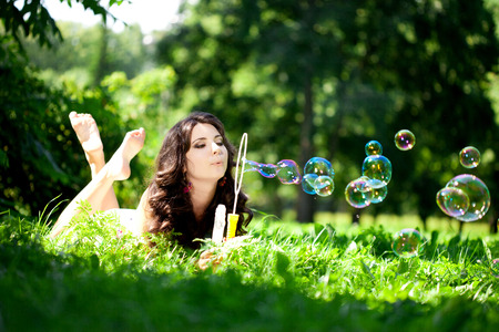 cute teen girl: Woman and soap bubbles in park. Beautiful young girl lying on the grass in the field. Smiling trendy stylish woman on nature  Stock Photo