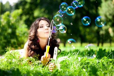 burbujas de jabon: Mujer y pompas de jabón en el parque. Hermosa joven tumbado en la hierba en el campo. Sonriente mujer con estilo de moda en la naturaleza