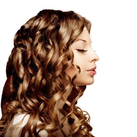 Makeup, hairstyle, curls. Young beautiful woman with luxurious curly hair. Modern stylish trendy girl with curls. photo