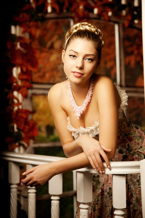 Young beautiful woman in vintage dress on autumn porch. Beauty girl in fall orange leaves  photo