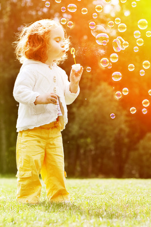 burbujas de jabon: Niño que sopla un pompas de jabón. Kid soplando burbujas en la naturaleza. Bebé al atardecer, los rayos del sol