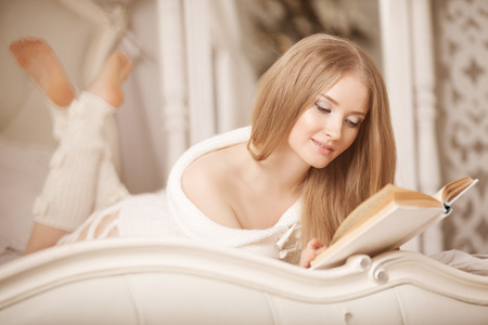 Beauty girl reading book. Beautiful young woman lying on the sofa reading a book in the bedroom. photo