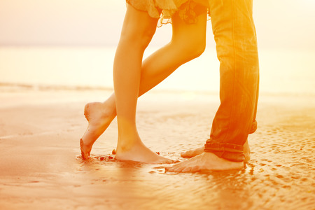 A young  loving  couple hugging and kissing on the beach at sunset.