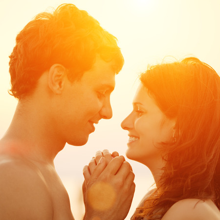 passion couple: A young  loving  couple hugging and kissing on the beach at sunset.