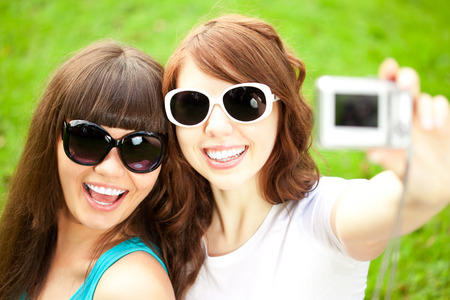 taking photograph:  Two young trendy girls doing selfie.