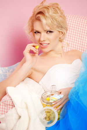 Cute woman looks like a doll in a sweet interior.  photo