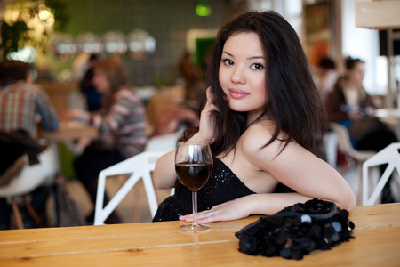 sexy asian girl: Young beautiful trendy woman in the bar. Beautiful Asian girl in a pub. Woman with alcohol.