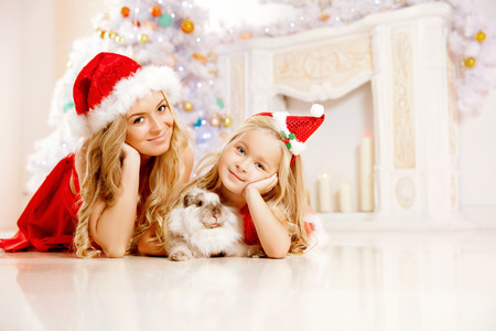 Mother and daughter dressed as Santa celebrate Christmas. photo
