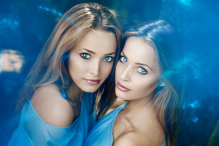 Two women face close-up. Trendy stylish sisters photo