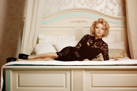 Beauty rich luxury woman like Marilyn Monroe. Beautiful fashionable girl in  retro interior in the bedroom on the bed photo