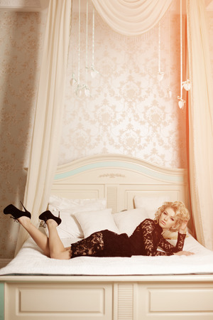 Beauty rich luxury woman like Marilyn Monroe. Beautiful fashionable girl in a retro interior in the bedroom on the bed  photo