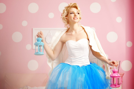 Cute woman looks like a doll in a sweet interior. Young pretty smiling girl photo