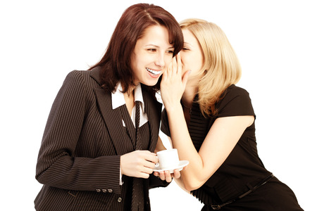 intrigue: Business gossip. Women in the office. Two girls discuss the news at lunchtime with coffee. Gossip, rumors, secrets and intrigue Stock Photo