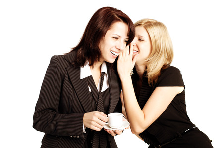 lunchtime: Business gossip. Women in the office. Two girls discuss the news at lunchtime with coffee. Gossip, rumors, secrets and intrigue Stock Photo