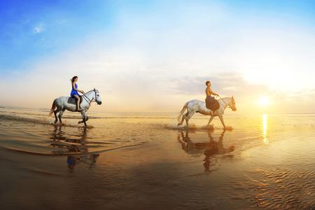 caballo de mar: El amor de fondo. Familia y caballo en la luz del sol. Pareja de enamorados en la playa en la puesta del sol. Paseo a caballo del mar en los rayos del sol. Foto de archivo