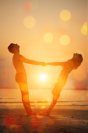 Summer fun holyday on beach background. A loving young couple hugging and kissing on the beach at sunset. Two lovers, man and woman near the water. Summer  scene in love  sunset sky Reklamní fotografie