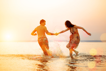 Verano divertido Holyday en el fondo playa. Pareja de enamorados en la fiesta en la playa. Escena de verano sobre el cielo del atardecer.