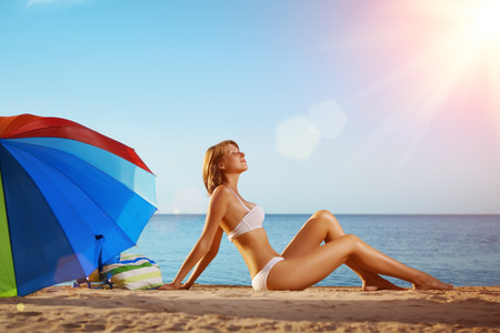 smiling sun: Summer fun holiday woman on summer landscape with rainbow umbrella. Girl with tanned body lying on the beach under the sun and blue sky