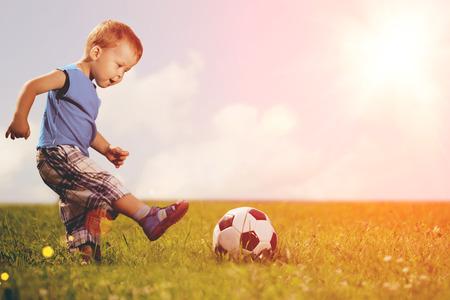 patada: Chico Deportes. Muchacho que juega al fútbol. Bebé con la bola en el campo de deportes. Juegos de niños.