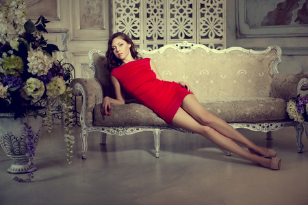 Slim trendy, luxurious, fashion woman in  lux vintage interior. Girl in red short dress on a luxury background