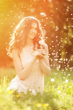 Young spring fashion woman blowing dandelion in spring garden. Springtime. Trendy girl at sunset in spring landscape background. Allergic to pollen of flowers. Spring allergy Stock Photo
