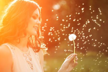 lifestyle: Mujer de moda de primavera joven que sopla el diente de león en el jardín de primavera. Primavera. Moda niña al atardecer en el fondo del paisaje de primavera. Alérgica al polen de las flores. Alergia a la primavera