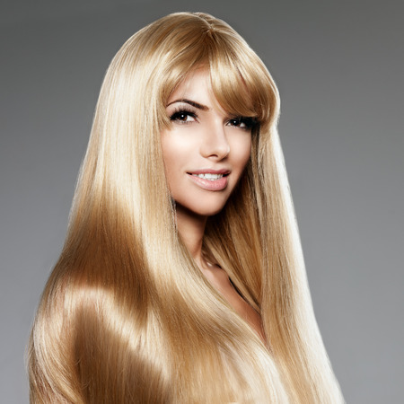 blond hair: Beauty young woman with luxurious long blond hair. Haircut with fringe. Girl with fresh healthy skin, prifessional  makeup, red lips, long eyelashes and manicured nails shiny. Fashion model in spa hair care salon.  Girly sexy  trendy hairstyle look. Stock Photo