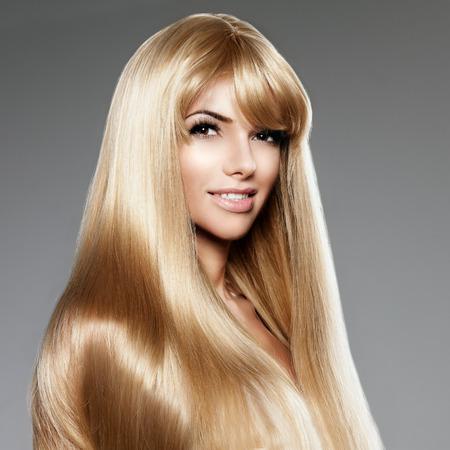 Schoonheid jonge vrouw met luxe lange blonde haren. Kapsel met franje. Meisje met verse gezonde huid, prifessional make-up, rode lippen, lange wimpers en gemanicuurde nagels glanzend. Mannequin in de spa haarverzorging salon. Girly sexy trendy kapsel look.