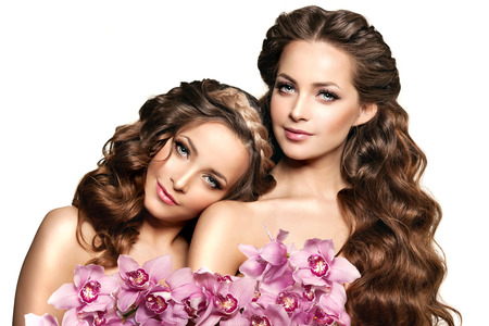 two face: Two beauty young women, luxury long curly hair with orchid flower. Haircut. Beautiful girls fresh healthy skin, makeup, lips, eyelashes. Fashion models in spa care salon. Sexy trendy hairstyle look.