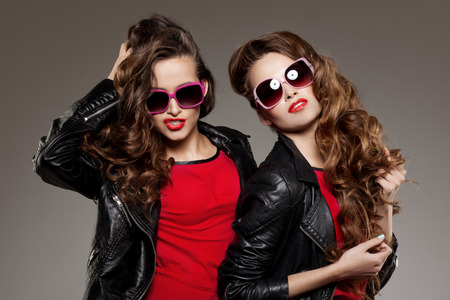 two friends talking: Sisters twins in hipster sun glasses laughing Two fashion models Women smiling positive Friends group having fun, talking Youthful friendship youth adults people culture concept Young girls rock party Stock Photo