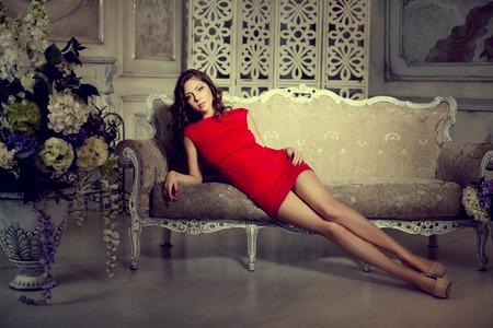 moda: Slim moda, lusso, moda donna in lux interni d'epoca. Ragazza in abito corto rosso su uno sfondo di lusso