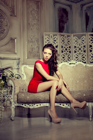 girl in red dress: Slim trendy, luxurious, fashion woman in  lux vintage interior. Girl in red short dress on a luxury background