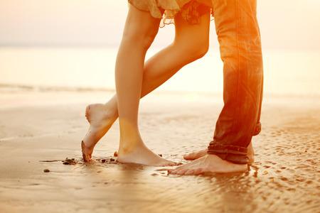 Een jong liefdevolle paar knuffelen en kussen op het strand bij zonsondergang. Twee geliefden, man en vrouw op blote voeten in de buurt van het water. Zomer in de liefde
