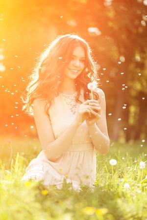 若い春のファッション女性の春の庭のタンポポを吹きます。春。春の風景の背景の夕日のトレンディな女の子。花の花粉にアレルギーがあります。 写真素材