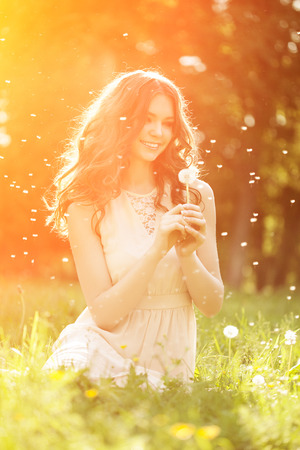 Young spring fashion woman blowing dandelion in spring garden. Springtime. Trendy girl at sunset in spring landscape background. Allergic to pollen of flowers. Spring allergy Foto de archivo