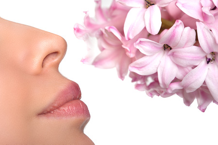 Close-up nose and a flower. Allergy to pollen of flowers. asthma attack. Floral fragrance, perfumes Stock Photo