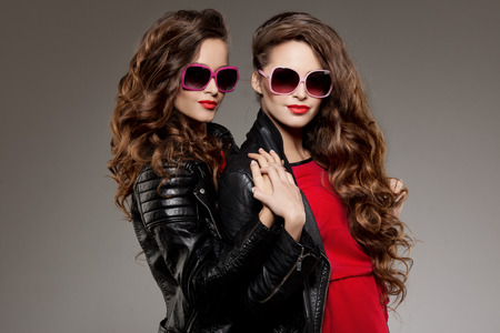 woman fashion: Sisters twins in hipster sun glasses laughing Two fashion models Women smiling positive Friends group having fun, talking Youthful friendship youth adults people culture concept Young girls rock party Stock Photo