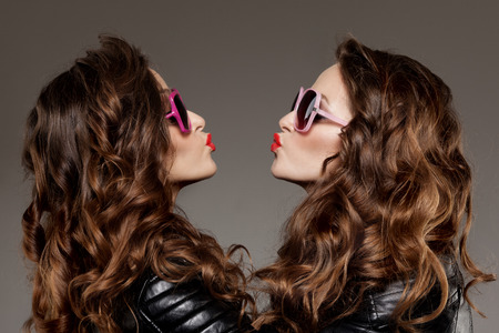 youthful: Sisters twins in hipster sun glasses laughing Two fashion models Women smiling positive Friends group having fun, talking Youthful friendship youth adults people culture concept Young girls rock party Stock Photo