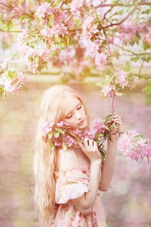 春の庭で若い春ファッション女性。春。春の風景の背景の夕日のトレンディな女の子。花の花粉にアレルギーがあります。春のアレルギー