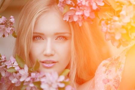 Mujer de moda de primavera joven en el jardín de primavera. Primavera. Moda niña al atardecer en el fondo del paisaje de primavera. Alérgica al polen de las flores. Alergia a la primavera Foto de archivo