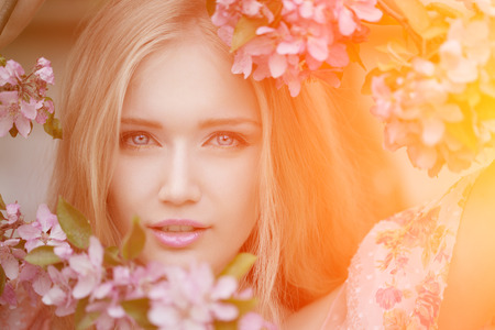 meadows: Young spring fashion woman  in spring garden. Springtime. Trendy girl at sunset in spring landscape background. Allergic to pollen of flowers. Spring allergy