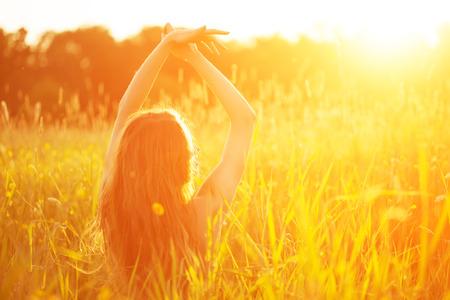 流行に敏感な若いモデル美容女性、長い髪を吹きます。春や夏の日没のフィールドでのカジュアルな女の子の背景の風景。春。夏。花の花粉にアレ 写真素材