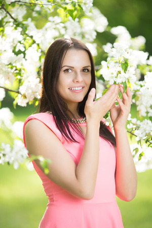young beautiful woman: Young spring fashion woman. Trendy girl in the flowering trees in the spring summer garden. Springtime or summertime. Lady in spring landscape background. Allergic to pollen of flowers. Spring allergy