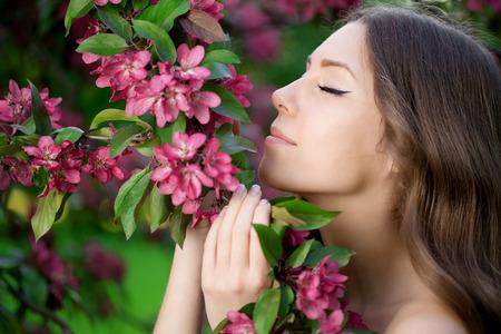 Junge Frühling Mode Frau im Frühjahr Garten Springtime Summertime Modisches Mädchen in den blühenden Bäumen in dann bei Sonnenuntergang im Frühjahr Landschaft Sommer Hintergrund Pollenallergiker von Blumen Allergie Standard-Bild