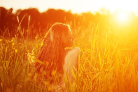 campo de flores: Modelo de mujer inconformista Chica joven casual en campo en la puesta del sol en primavera, fondo paisaje de verano primavera verano. Alérgica al polen de las flores Alergia retroiluminada Sun Light Autumn Glow Sun Sol